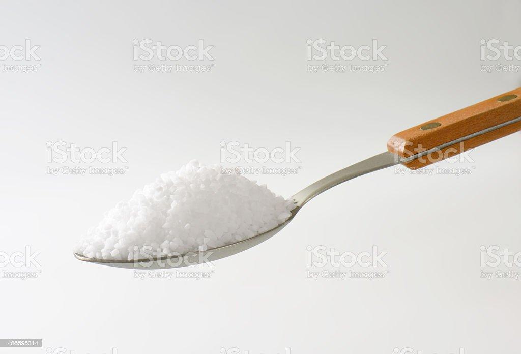Spoonful of coarse salt stock photo