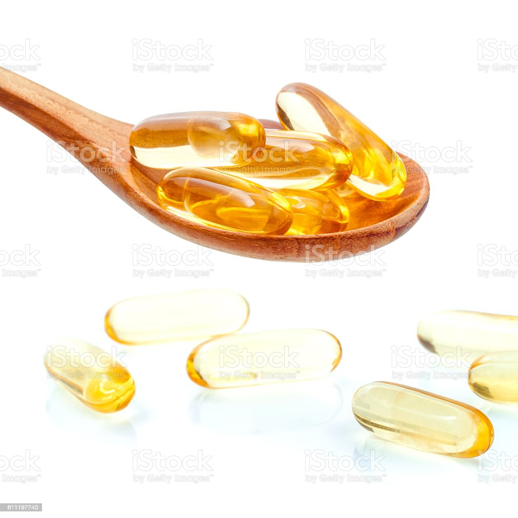 Spoonful of gel capsules of omega 3. stock photo