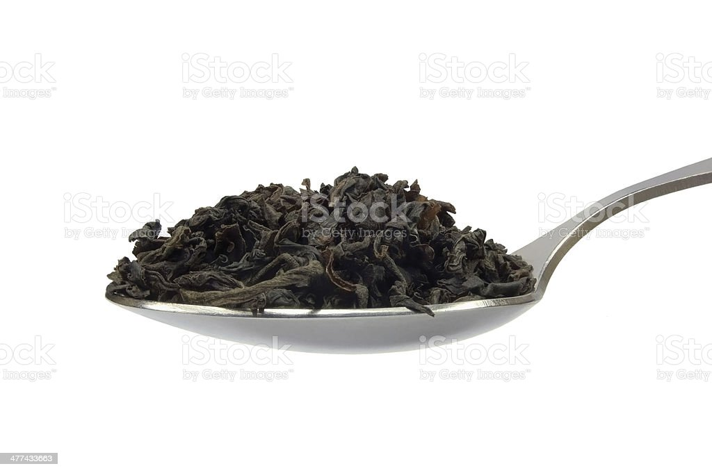 Spoonful of loose black tea leaf, detailed isolated macro closeup stock photo