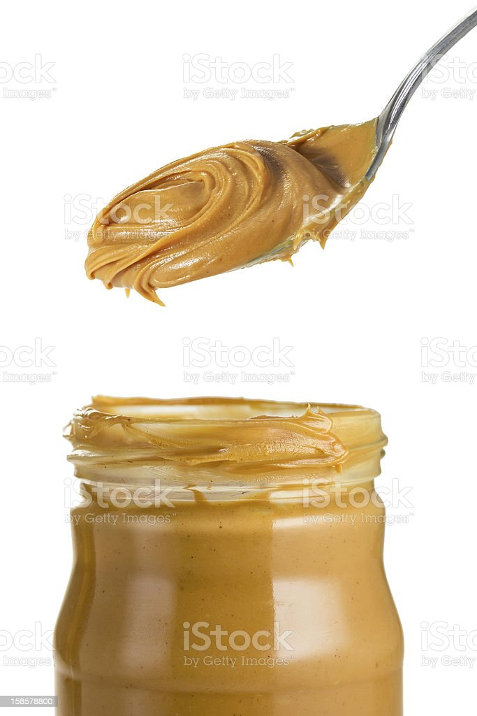 Spoonful of peanut butter hovering above jar stock photo
