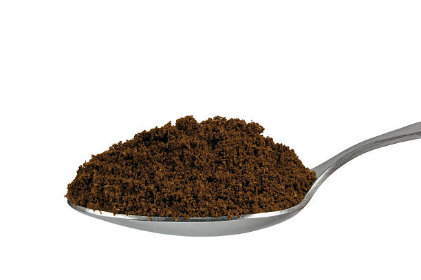 Spoonful of roasted Arabica coffee for espresso, teaspoon isolated closeup stock photo