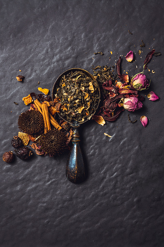 Spoonful of tea blend with rose buds, hibiscus leaves, echinacea flowers and cinnamon sticks on black rustic background