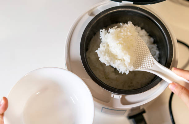 spooning rice from electric cooker stock photo