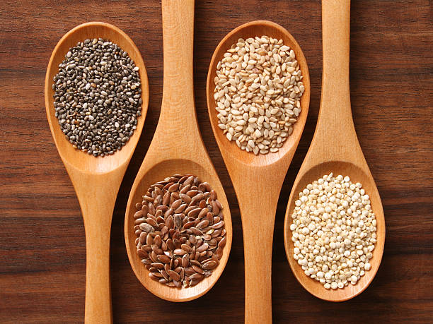 spoons and healthy seeds - chia seed stock photos and pictures