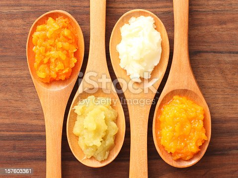 Four spoons with purees on them. From left to right: carrot, sweet potato, potato, squash