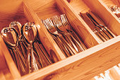 Spoons, forks, knives in the tray. Wooden drawer with modern cutlery. Kitchen or restaurant concept background