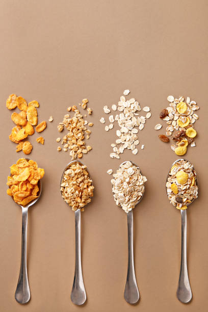 Spoons of various cereals view from above. Corn flakes, oat flakes, muesli, granola assortment. Top view - foto stock