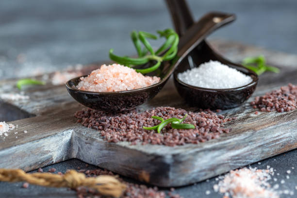 Spoons with white, pink Himalayan and black salt. stock photo
