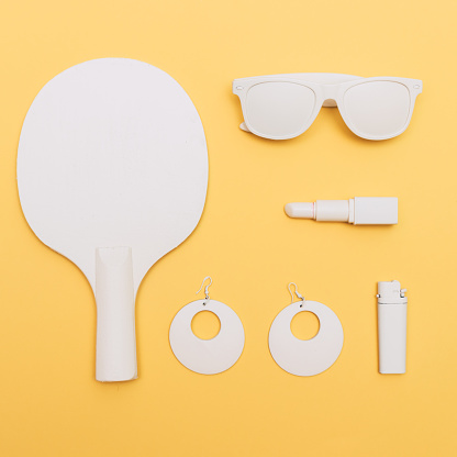 flat lay woman fashion set of white goods: sunglasses, lipstick, earrings and tennis racket. yellow background.