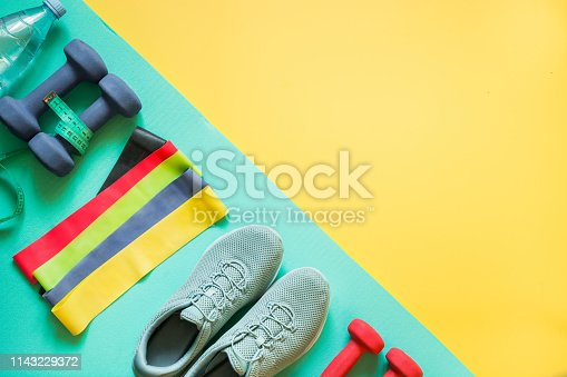 Sport and fitness equipment, rubber band, dumbbells, fitness shoes, measuring tape on punchy yellow. View from above, space for text.