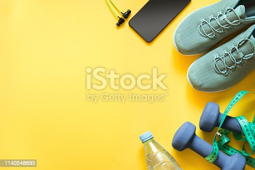 Sport and fitness equipment with sneakers and headphones on yellow. Top view, space for your text.