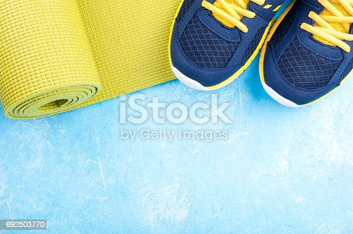 637596492 istock photo Sport and healthy lifestyle concept. Yoga mat and sport shoes on light background. Sport equipment 692503770