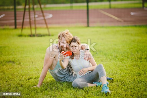 Sport and technology. Young in love heterosexual Caucasian couple resting after workout outdoors in park on lawn, green grass sitting in embrace and making selfie photo on smartphone camera at sunset.