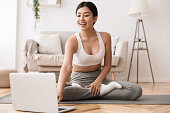 Sport application. Asian girl practicing yoga and using laptop at home, copy space