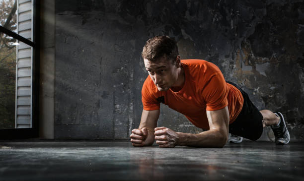 Sport background. Handsome man doing plank.