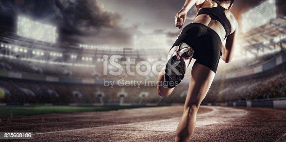 istock Sport background. Runner on the stadium. Dramatic scene. Back view. 825608186