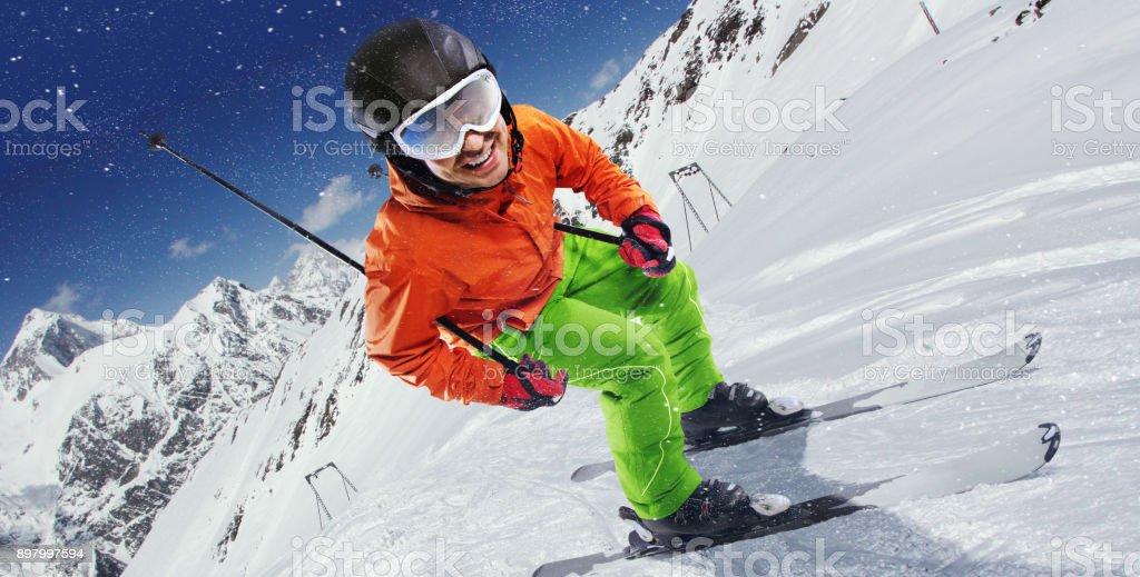 Skier on piste running downhill in beautiful Alpine landscape. Blue...