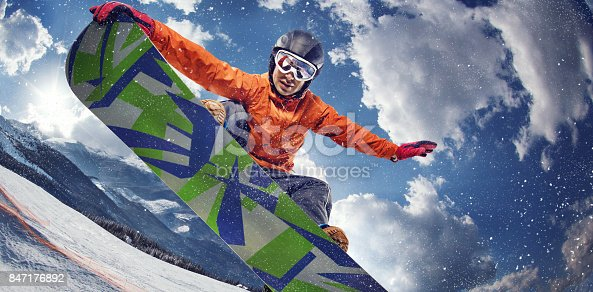 istock Sport background. Winter sport. Snowboarder jumping through air with deep blue sky in background. 847176892
