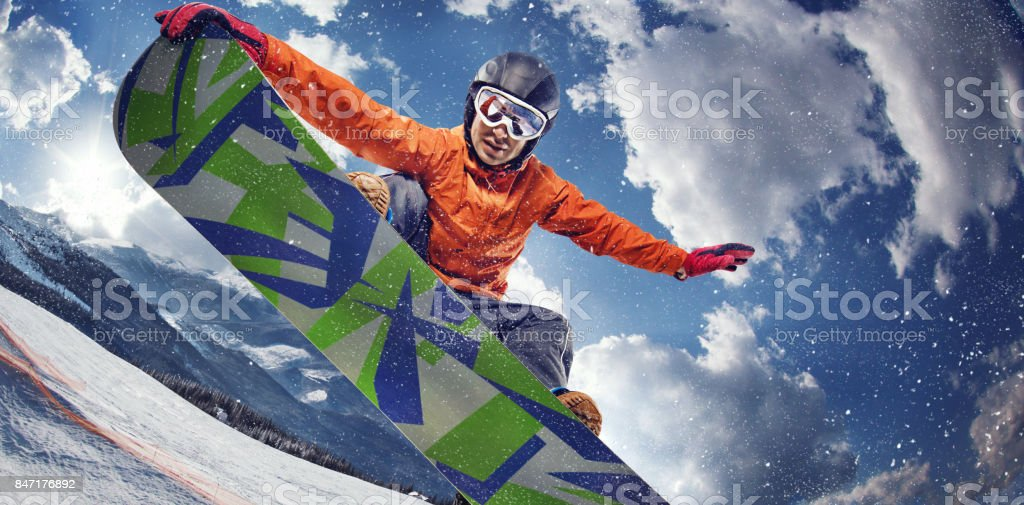 Sport background. Winter sport. Snowboarder jumping through air with deep blue sky in background. stock photo