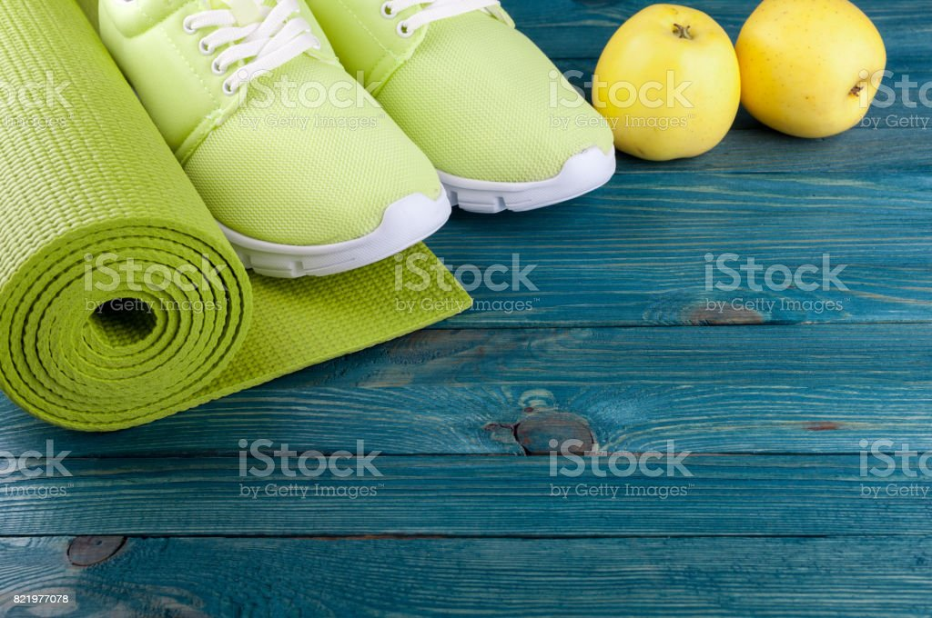 668b0e7922c36 Sport background. Yoga mat, sport shoes, apples fruits on wooden background.  Healthy