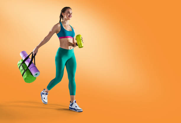 Sport backgrounds. Beautiful slim sporty young girl is preparing for joint training. Fitness concept.