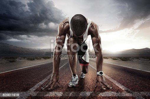 istock Sport backgrounds. Sprinter on the start line of the track befor the dramatic sky. 825611618