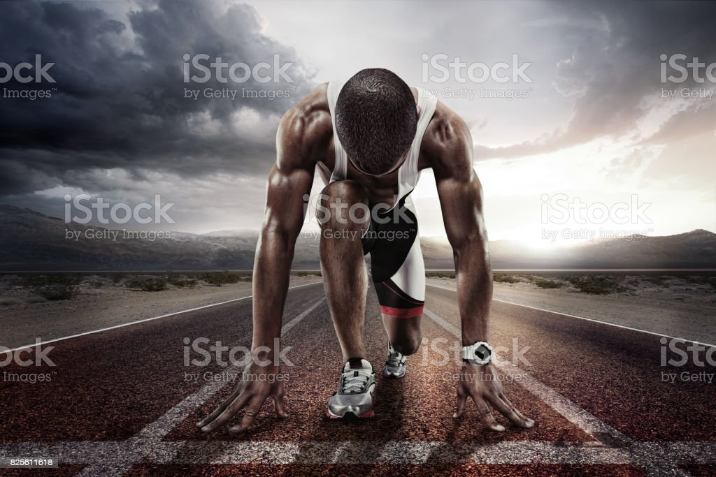 Sport backgrounds. Sprinter on the start line of the track befor the dramatic sky. stock photo