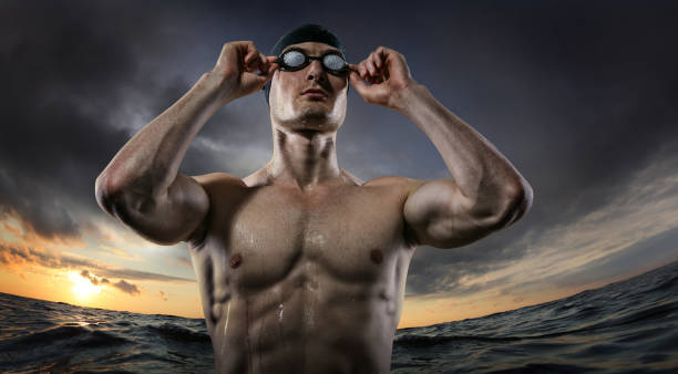 Sport backgrounds. Young athletic swimmer standing near the sunset river. Dramatic scene.