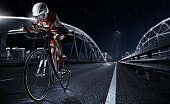 istock Sport backgrouns. Athletic woman cycling road bike in the evening. Dramatic view of the night city. 825608196