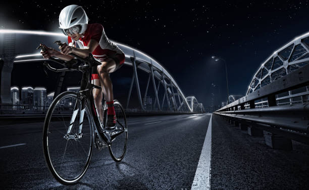sport backgrouns. athletic woman cycling road bike in the evening. dramatic view of the night city. - bike tire tracks foto e immagini stock