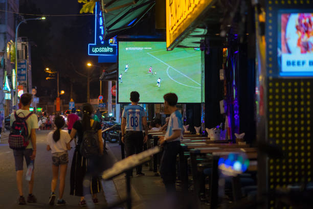 sport bar exterior, with a tv screen with football broadcast at night - serie televisiva foto e immagini stock