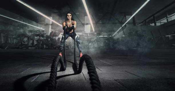 運動。戰鬥繩索會話。有吸引力的年輕健身運動的女運動員工作在功能訓練健身房做運動與戰鬥繩索。 - 健身房 個照片及圖片檔