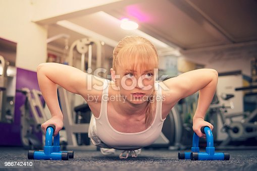 Sport. Beautiful woman in the gym. Cute cute blonde while doing push-UPS on a special push-up simulator. gym