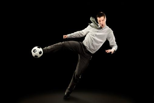 sport business man plays soccer football on black background