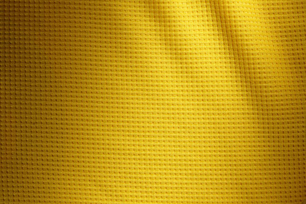 Sport Clothing Fabric Texture Background. Top View of Cloth Textile Surface. Yellow Football Shirt. Text Space stock photo