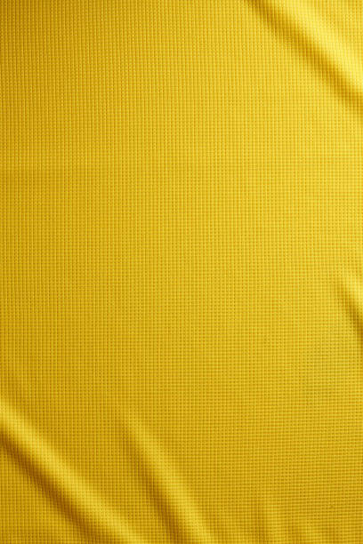 sport clothing fabric texture background. top view of cloth textile surface. yellow football shirt. text space - textile stock photos and pictures