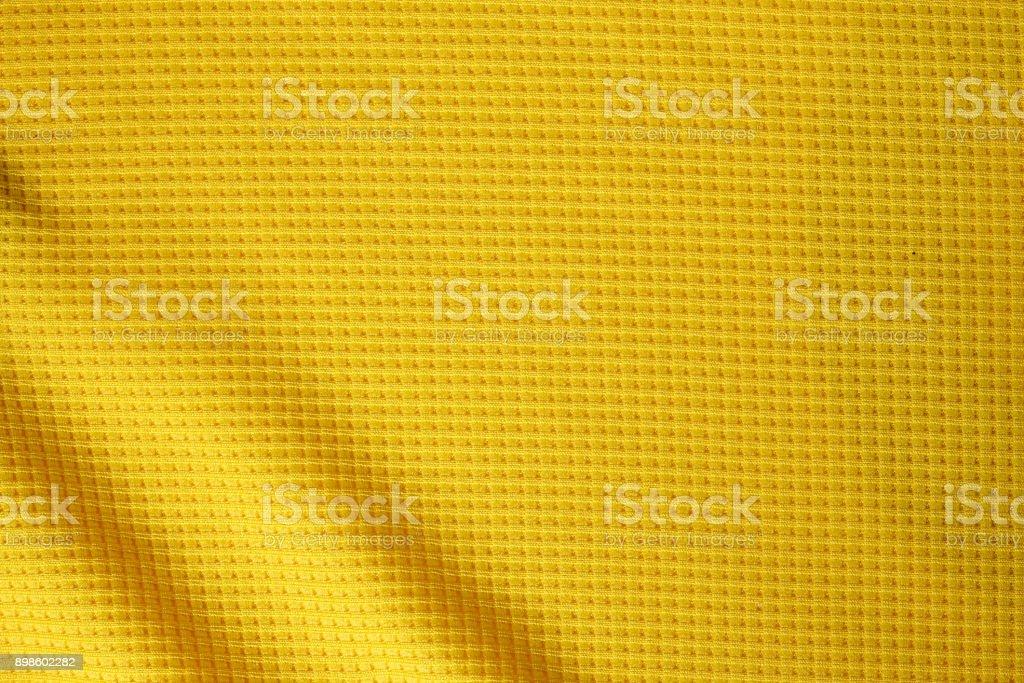 Fundo de textura tecido roupa esporte. Vista superior da superfície do pano têxtil. Camisa de futebol amarelo. Espaço de texto - foto de acervo