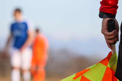 Sport concept. Soccer, football assistant referee is standing and holding the flag. Blurred sky and players background. Part of the linesman.