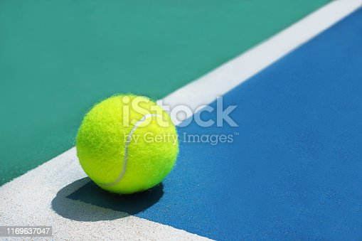 1153628111istockphoto Sport concept with tennis ball on white line in the corner of hard tennis court. 1169637047
