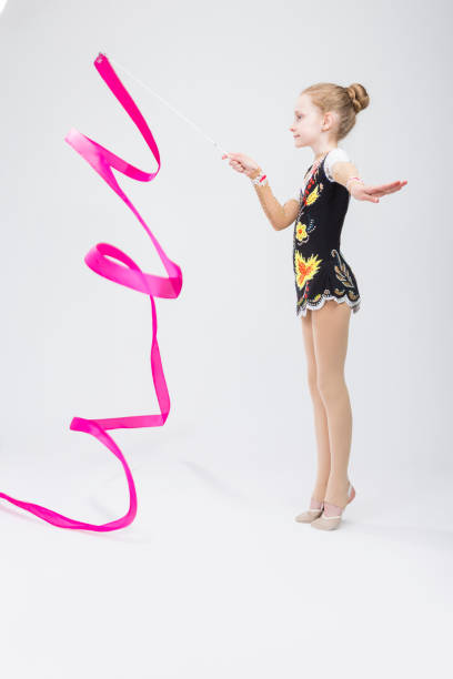 Sport Concepts. Little Caucasian Female Rhythmic Gymnast In Professional Competitive Suit Doing Artistic Ribbon Spirals Exercises in Studio Against White. Vertical Image Composition