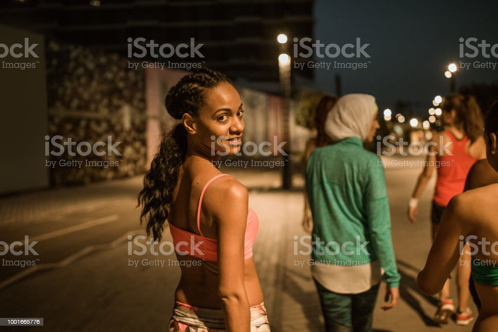 Multi ethnic group of young women exercise outdoor at night. One of...
