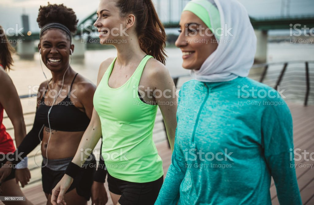 Multi ethnic group of young women exercise outdoor, next to the...