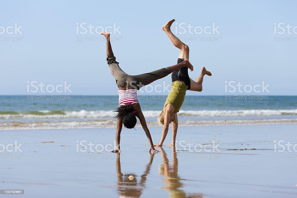 Sport couple doing gymnastics on the beach stock photo