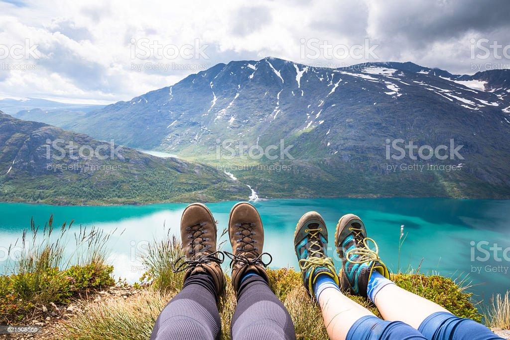 Sport couple hiking on Besseggen. Hikers enjoy beautiful lake and foto stock royalty-free
