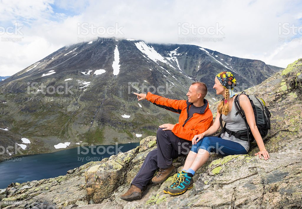 Sport couple hiking on Besseggen. Hikers enjoy beautiful lake and foto stock royalty-free