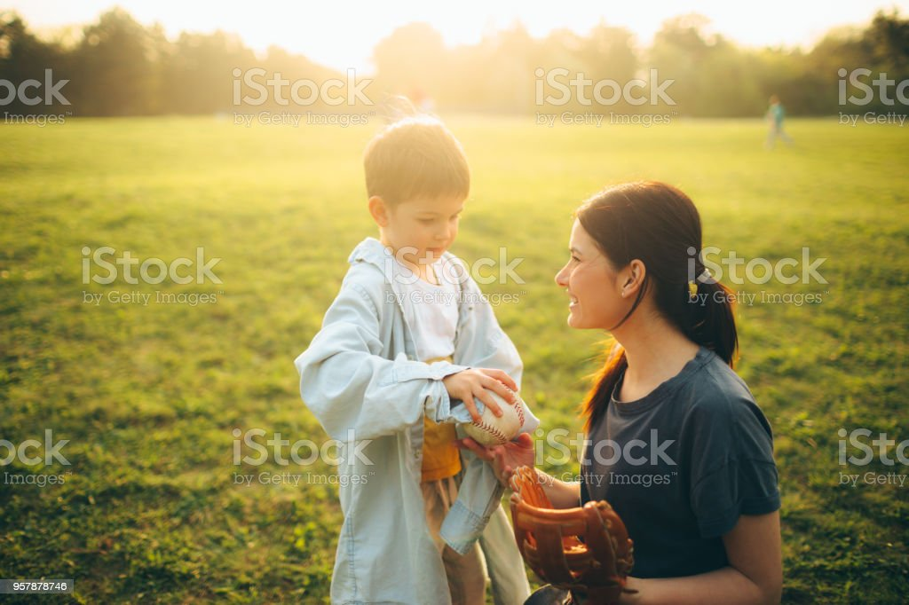 Mother and son having a sport day outdoors, playing catch