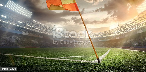 istock Sport. Empty football soccer field with white marks, green grass texture and orange corner flag. 936172324