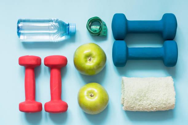 Equipamentos de esporte. Criativa na cama plana de equipamentos de esporte e fitness em fundo azul com espaço de cópia. - foto de acervo