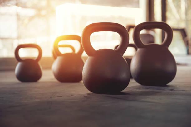 equipo del deporte en el gimnasio. kettlebell en el fondo piso, entrenamiento físico - pesa rusa fotografías e imágenes de stock