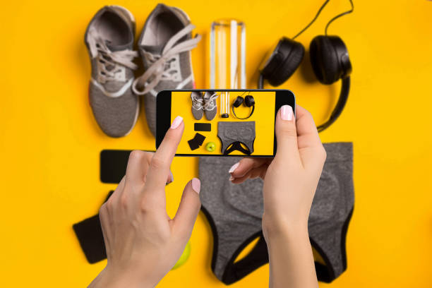 sportgeräte auf dem handy zu fotografieren. smartphone-bildschirm mit fitness tools bild - malerei schuhe stock-fotos und bilder